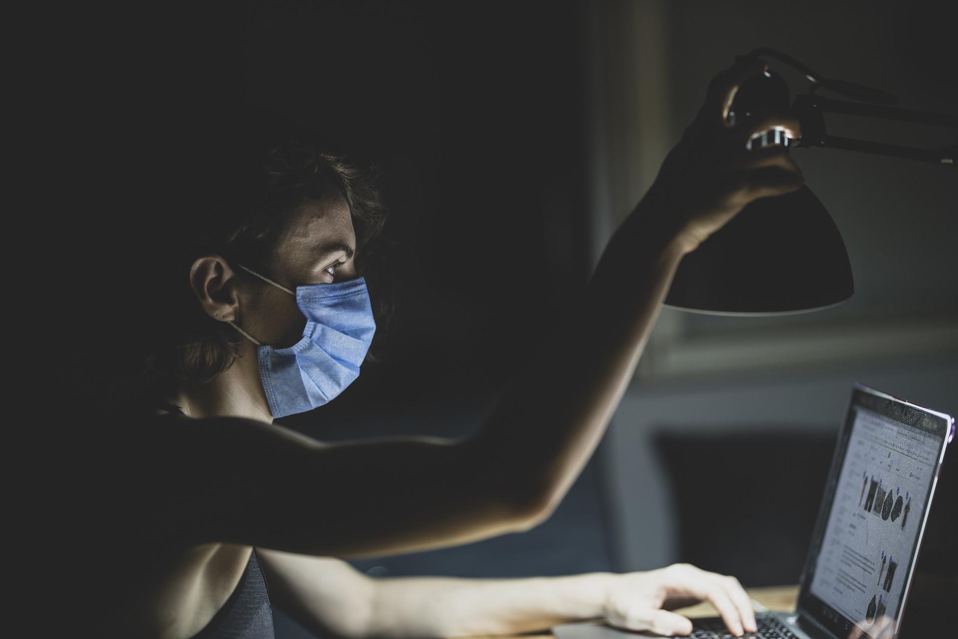 Joven con mascarilla prendiendo lámpara en escritorio